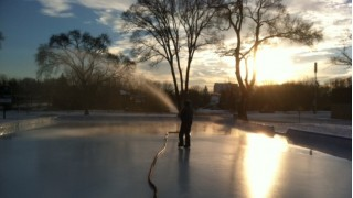 Morning coat of the park rink with a firehose