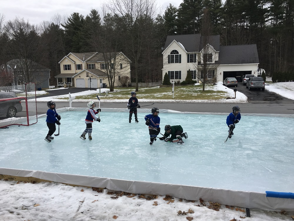Residential ice rink with kids playing hockey.  Rink built with an Iron Sleek Rink kit.