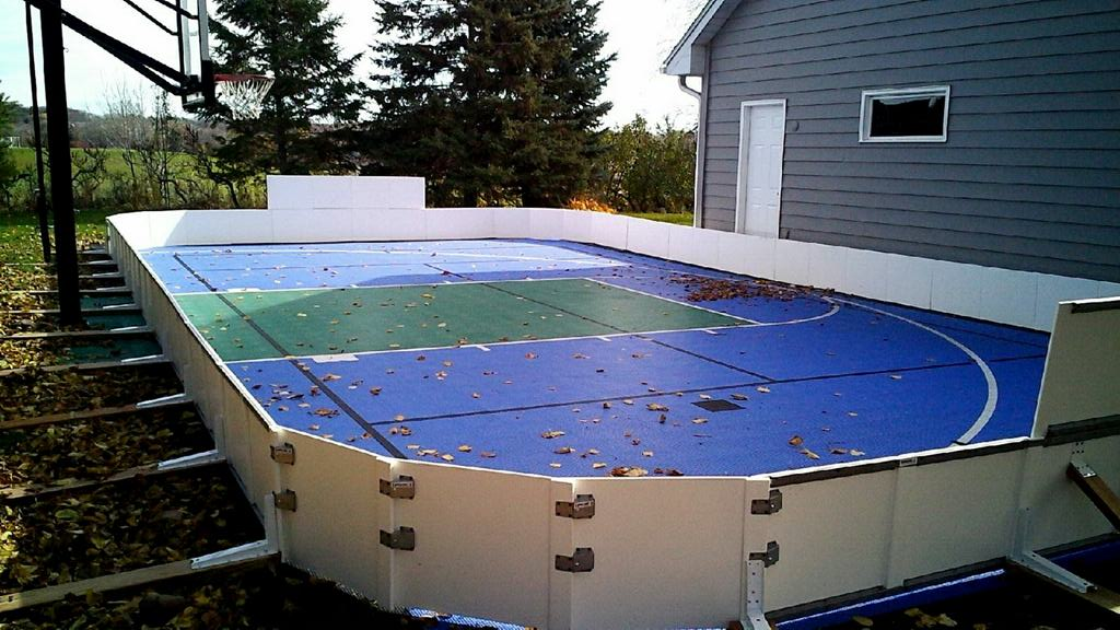 Backyard ice rink on a sports court using plastic side boards.