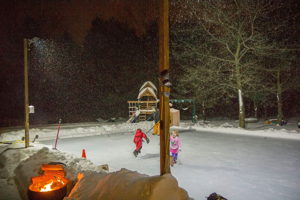 Kids skating under the lights and snow on a backyard rink.