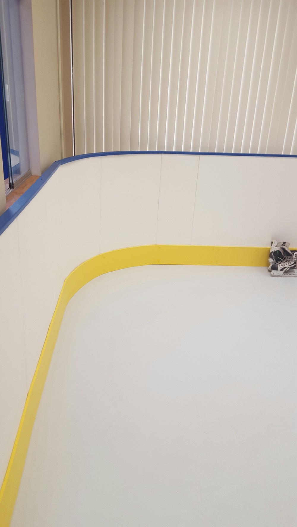 Synthetic ice rink with rounded corners.  42 inch tall white boards with yellow kicker.