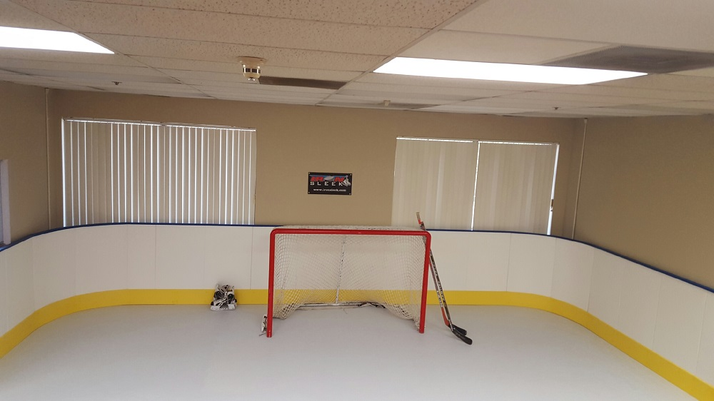 Synthetic ice in a rec room with 42 inch tall boards for hockey training or leisure.
